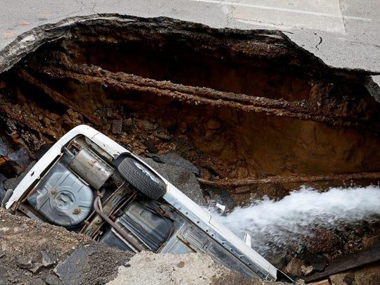 A Toyota Camry sits in a large hole in 6th Street,