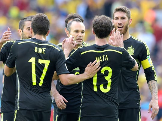 Spain's Juan Mata celebrates with teammates after scoring during the group B World Cup soccer match between Australia and Spain at the Arena da Baixada in Curitiba, Brazil, Monday, June 23, 2014. (AP Photo/Manu Fernandez)