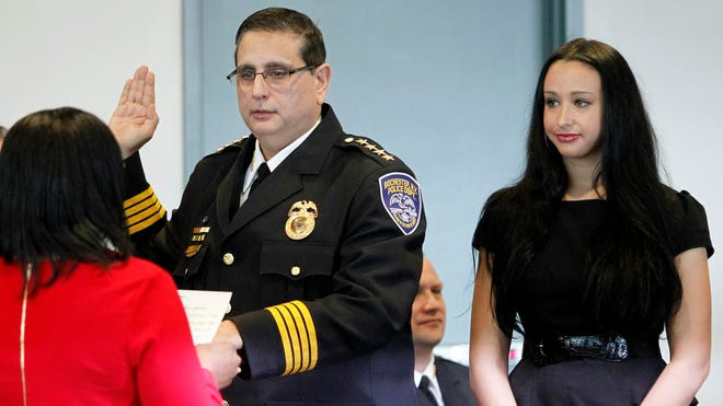 Mayor Lovely A. Warren, left, administered the oath of office to new Police Chief Michael L. Ciminelli in Rochester Saturday morning. Next to Ciminelli is one of his three daughters, Christina, who came up from Virginia to attend the ceremony.