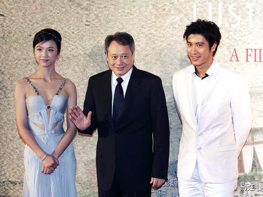 """Director Ang Lee, center, poses with Chinese actress Tang Wei, left, and actor Wang Leehom, right, before the premiere of their film """"Lust, Caution,"""" at the Shanghai Film Center in Shanghai, China on Wednesday Oct. 31, 2007."""