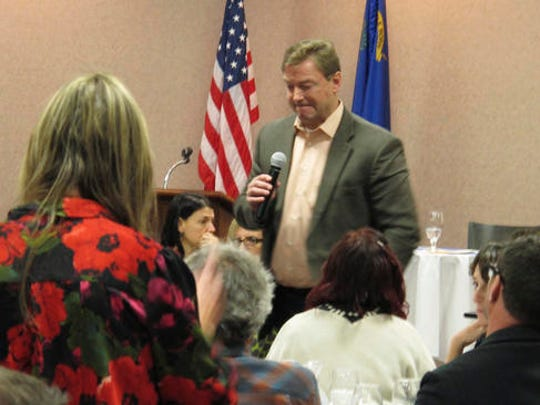 Sen. Dean Heller, R-Nev., listens to a question from a woman standing in the foreground critical of his support for President Donald Trump's Cabinet nominees on Wednesday, Feb. 22, 2017, during a Carson City Chamber of Commerce luncheon in Carson City, Nev. About 200 protesters clamored outside a casino Wednesday in Nevada's capital where two Republican members of the state's congressional delegation are scheduled to speak with business leaders. Muffled jeers could be heard as Heller and Rep. Mark Amodei spoke about the congressional session at the luncheon. (AP Photos/Scott Sonner)