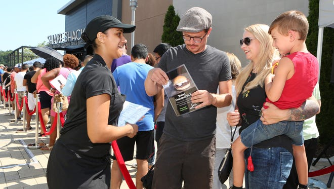 Team member Kassandra Leon passes out menus to John James, Coda, 4 1/2 and Jessie Slater waiting on line, as Westchester's first Shake Shack prepares to open at the Cross County Shopping Center in Yonkers, July 22, 2016.
