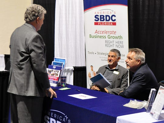 Marc Farron, center, and Russ Winstead, right, talk to someone at the booth for the Florida Small Business Development Center, part of the LEARN kickoff and partner expo at Harborside Event Center in Fort Myers.