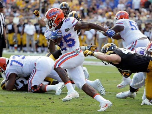 """FILE - In this Jan. 2, 2017, file photo, Florida running back Jordan Scarlett (25) eludes a tackle by Iowa defensive lineman Parker Hesse (40) during the first half of the Outback Bowl NCAA college football game in Tampa, Fla.  Scarlett and three other Florida players suspended last season amid felony fraud charges have rejoined team activities. School officials confirmed the return of the players Tuesday, Jan. 23, 2018, to The Associated Press. Coach Dan Mullen says """"all of our players understand the standards and expectations we have of them to be members of the Florida football program."""" (AP Photo/Chris O'Meara, File)"""