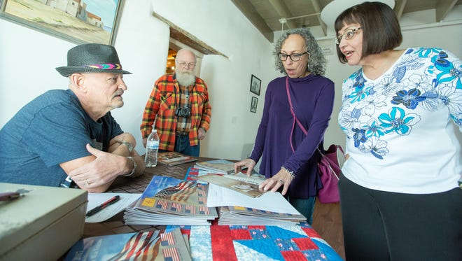 Christina Cavez Kelley, far right, and Celina Garcia Einig, purchase Doña Ana historical calendars from Rod Blanchard, far left, and Pete Drexler, on Saturday February 4, 2017 at the De La O center.  All fund made from the calendar sale will go towards renovating the Doña Ana Cemetery.