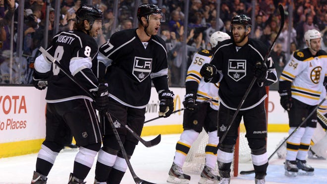 Los Angeles Kings center Jeff Carter celebrates with defenseman Drew Doughty and left wing Dwight King after scoring a goal in the first period.