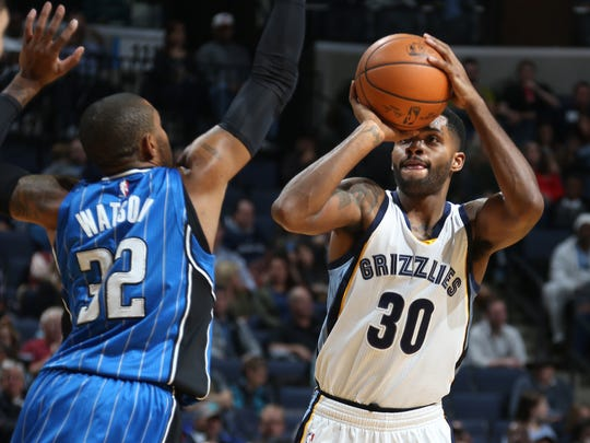 Memphis Grizzlies guard Troy Daniels, right, takes an outside jump shot defended by Orlando Magic guard C.J. Watson, left.