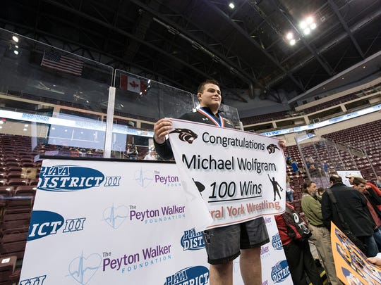 Central York's Michael Wolfgram holds up a '100 wins' sign after earning his 100th win during his tech-fall victory in the 285-pound AAA championships at Hershey's Giant Center for the District 3 tournament, Saturday, Feb. 24, 2018.