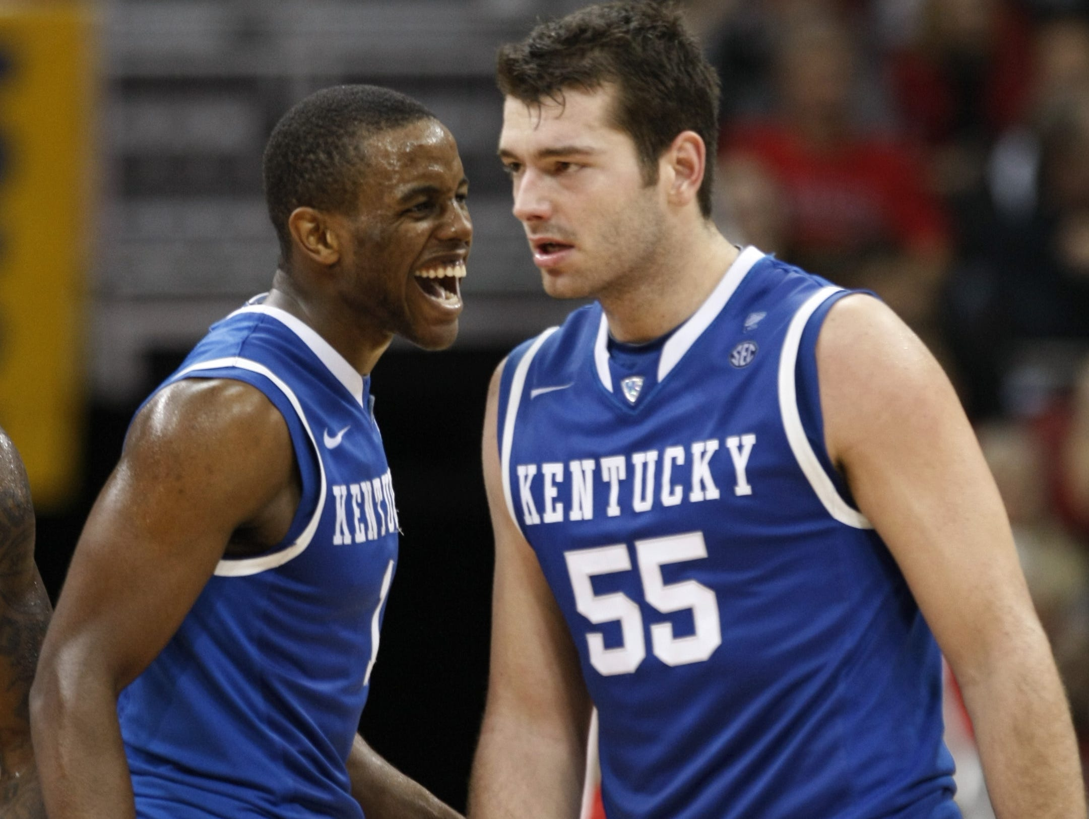 Kentucky's Josh Harrellson (55) is congratulated by teammate Darius Miller after hitting a shot during the second half of an NCAA college basketball game against Louisville in Louisville, Ky., Friday, Dec. 31, 2010. Harrellson had 23 points and 14 rebounds in his team's 78-63 win. (AP Photo/Ed Reinke)