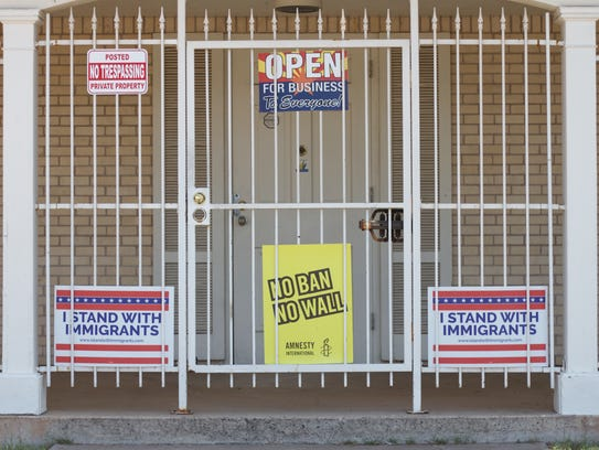 Immigration advocacy signs line the side of the First