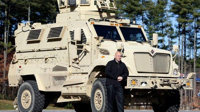 A former New York Undersheriff poses in front of a Mine-Resistant Ambush Protected vehicle that was acquired by the department in Queensbury, N.Y. under the military 1033 program in 2013.