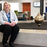 The Battle Creek Area Math and Science Center's new executive director, Susan Buckham, beside the Foucault pendulum in the school's lobby.