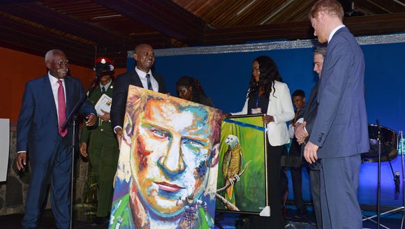 Prince Harry takes a look at his portrait by local