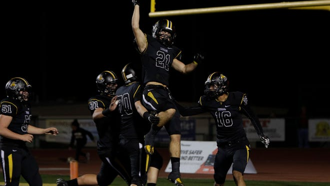Ventura High's Broc Mortensen (21) celebrates with his teammates after scoring a touchdown in the Cougars' playoff win over Moorpark on Friday night at Ventura.