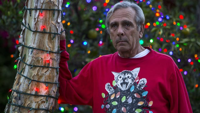 Lee Sepanek in front of Christmas lights he helped set up in his neighbor's yard in Phoenix. 2017 was the first time in 30 years he and his wife decided not to decorate their Arcadia home with more than 250,000 Christmas lights due to neighbor's complaints to the city.
