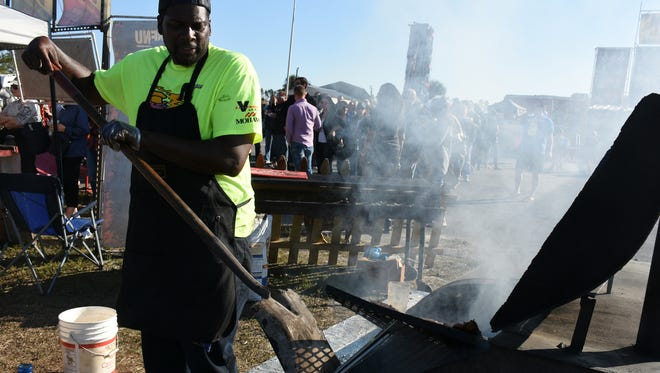 Rico Pace of the Smoke Shack stirs coals with a shovel at the barbecue competition.