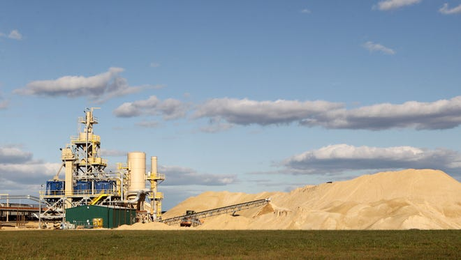 Piles of sand at Completion Industrial Minerals in Marshfield in August 2013.