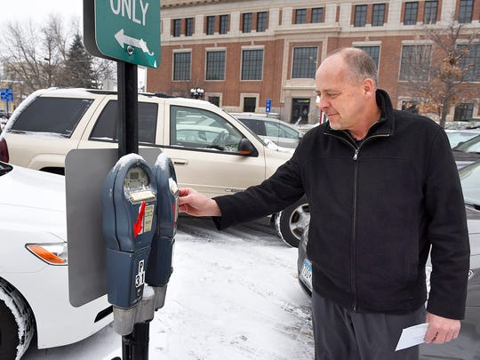Kevin Olson, Sauk Rapids, puts money in the parking meter Wednesday, Jan. 20, 2016, outside the Stearns County Administration Building.