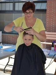 Joshua Noritsky, 8, of Millville gets a hair cut from