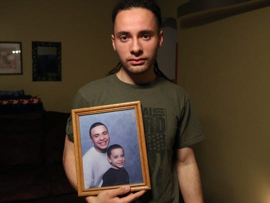 Zachary Laguerre at his Newburgh home holds a photo