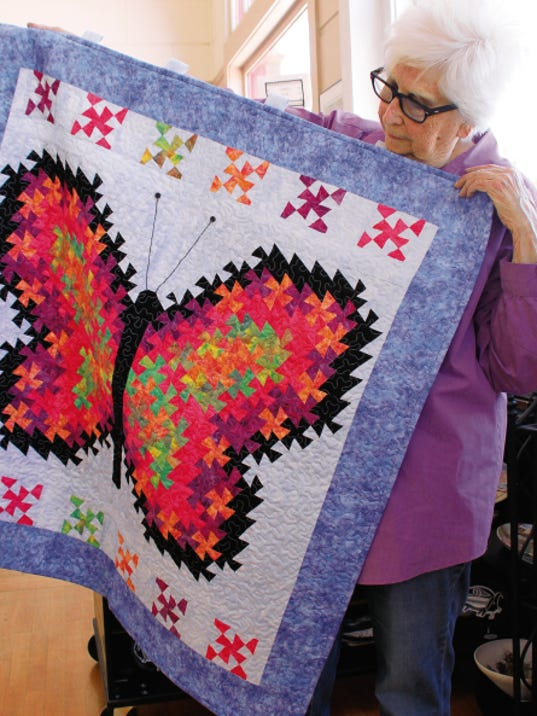 "Deming Art Council President Pat Guthrie unpacks a quilted wall tapestry done by Margaret Bagdon titled, ""Butterfly."" The Luna County Art Show on exhibit today at the Deming Art Center."
