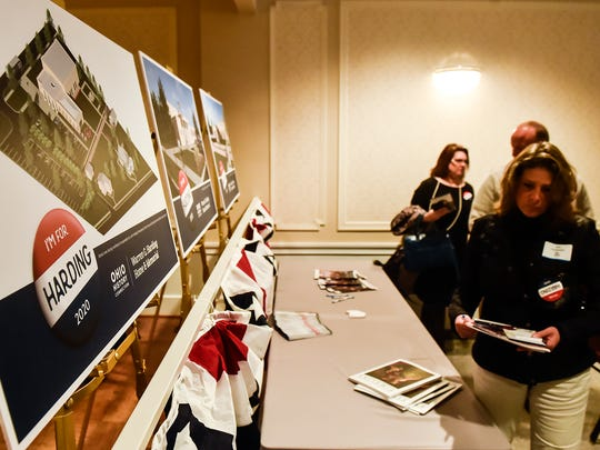 Attendees to the announcement of the Harding 2020 Project stop to look at the art designs for the project after the event on Tuesday.