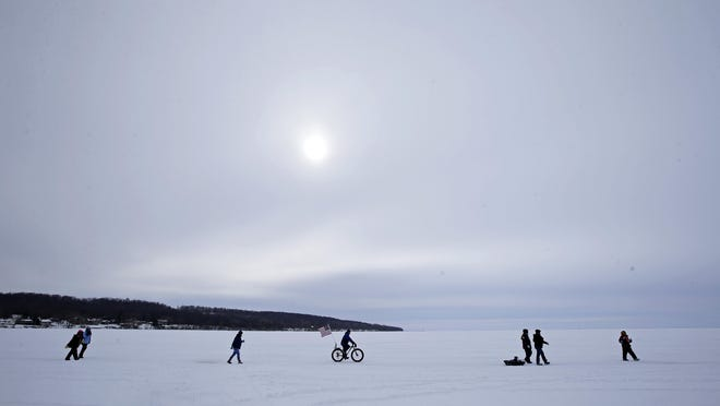 A winter sun offers little warmth to walkers and bicycle riders crossing Lake Winnebago near Faro Springs Road Beach as the Fox Cities Cycling Association 2017 Bike Across Bago and the Walk Across Lake Winnebago to benefit the Neenah Animal Shelter takes place on the ice Feb. 4 near Sherwood.