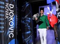 Serbia's Novak Djokovic, left, holds the Norman Brookes Challenge Cup after defeating Austria's Dominic Thiem in the final of the Australian Open tennis championship in Melbourne, Australia, Monday, Feb. 3, 2020. (AP Photo/Andy Brownbill)