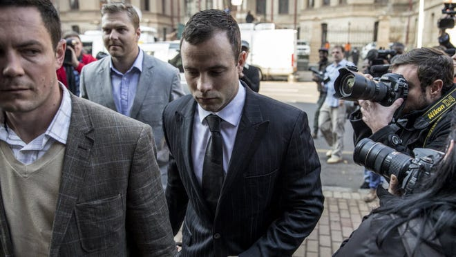 South African Paralympian Oscar Pistorius, center, arrives in court in Pretoria on June 30.