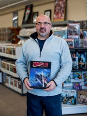 Kevin Knight, owner of Knight's Comics & Games, holds one of his favorite books, the Traveller Core Rulebook, at his store in Henderson, Ky., on Saturday, Nov. 11, 2017.