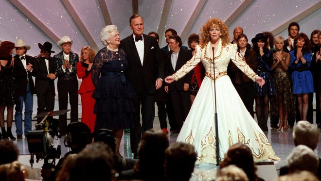 Host Reba McEntire, center, with President George and Barbara Bush, left, and other stars looking on, close out the 25th annual CMA Awards show at the Grand Ole Opry House Oct. 2, 1991.