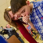 Resourse Teacher Kaitlyn Baetsle helps third-grader Nicolae Saybert decide on his vote on Monday, February 1, 2016, during the Cookie Caucus at Hillis Elementary School.