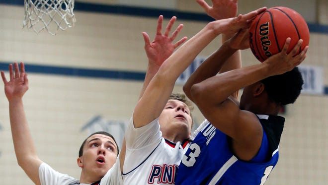 Pinnacle's  A.J. Elliot (left), and Ben Wahlberg (center)  guard Chandler's Riley McKinnis during a Division I state basketball tournament first-round game at Pinnacle High School in Phoenix on Feb. 19, 2015.