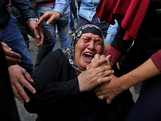 A woman cries during a protest after a judge on Saturday dismissed the case against former President Hosni Mubarak and acquitted his security chief over the killing of hundreds of protesters during Egypt's 2011 uprising, near Tahrir Square,Cairo, Egypt, Saturday, Nov. 29, 2014.