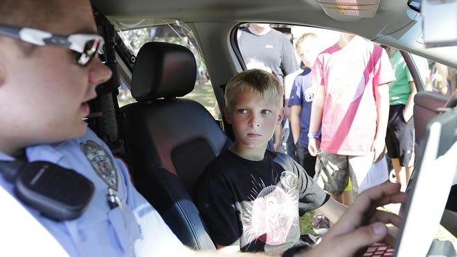 Community Service Officer Marcus Clapper explains the inside of a squad car to Levi Shaeffer of Fond du Lac, at the National Night Out at Fairgrounds Park.
