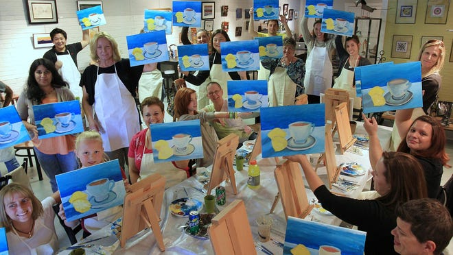 The class holds up their finished or almost finished painting during a Paint it with Pinot art class at Soho Cafe in Carmel in 2012.