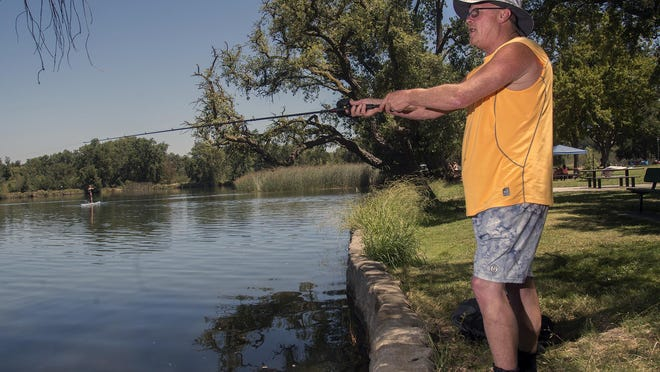 Dan Rakers spends his Fourth of July fishing from the banks of Lodi Lake Park.