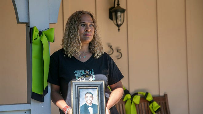 Taun Hall stands on the porch of her Walnut Creek home next to a green ribbon, the international symbol for mental health awareness. She and some of her neighbors display the ribbons in remembrance of her son, Miles, who was killed last year by Walnut Creek police during a mental health crisis.