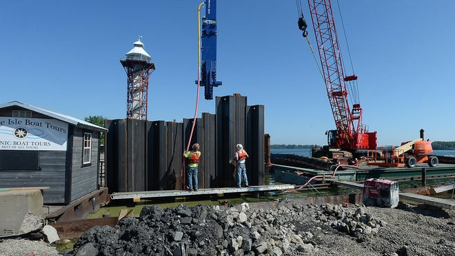 Ironworkers use a pile driver to set 26-foot sections of steel into the bedrock of Presque Isle Bay on Tuesday.