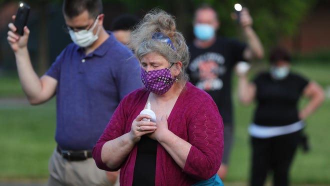 Citizens hold candles and cell phone lights during a moment of prayer held in honor of George Floyd and other victims of police brutality at the Veterans Memorial Park, Wednesday, June 10, 2020, in Green, Ohio.