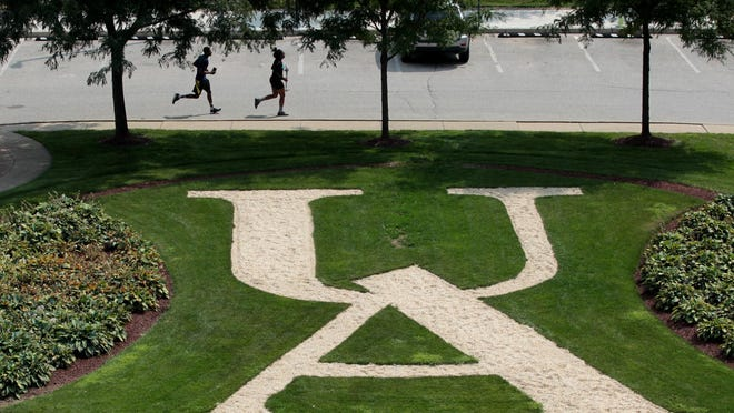 Students jog past a University of Akron emblem behind the Jean Hower Taber Student Union on Carroll Street on Wednesday, Aug. 15, 2018.