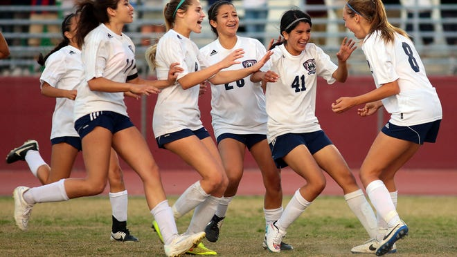 La Quinta players rush Jaylene Manion (8, right) after the Blackhawks defeated Ocean View with penalty kicks during a CIF quarterfinal playoff game on Thursday, February 26, 2015 at La Quinta. The game ended in a tie, 1-1, and remained that way through two overtime periods. La Quinta won on penalty kicks, 4-1, with Manion's kick sealing the win.