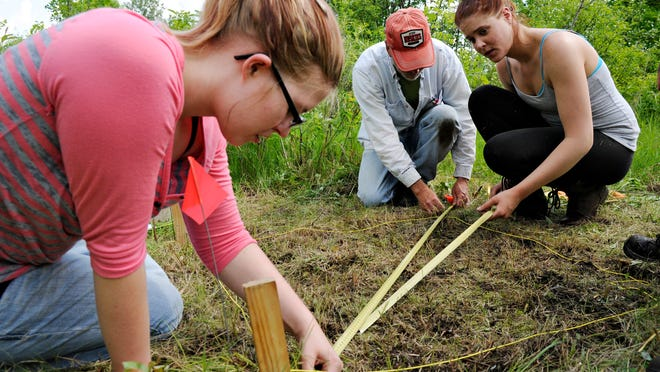 St. Cloud State University students Cassie Erickson (left) and Rachel Gramith (right) work with Rob Mann, assistant professor of anthropology, to lay out the first plot at a new site at the Little Elk River Mission site near Little Falls Wednesday, June 4.