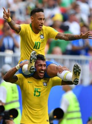 Neymar celebrates with teammate Paulinho.