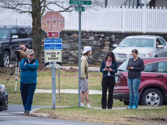 Concerned people gather at the perimeter during a lockdown