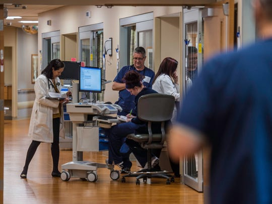 Doctors and nurses interact in a hallway in the Reid