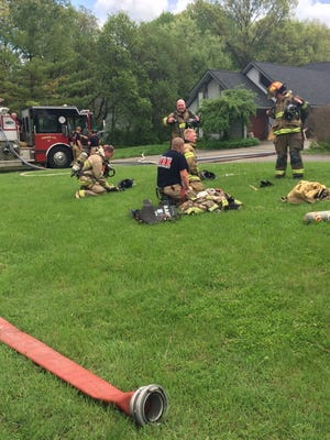 Brighton Area firefighters catch their breath Monday afternoon while battling at blaze at a house on Young Drive in Brighton Township.