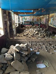 Piles of rubble sit in a classroom in a school in Namche