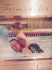 Joe Marciano and son Joseph swim in a pool.