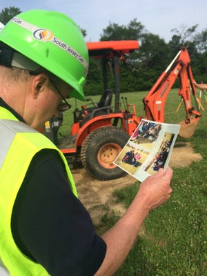 A South Jersey Gas site manager looks at photos from the 1991 time capsule burying ceremony before digging.